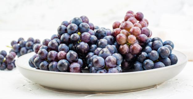 Digestiones pesadas en Navidad: cómo evitarlas: bayas uvas azules maduras plato sobre mesa 107288 1464 - HeelEspaña