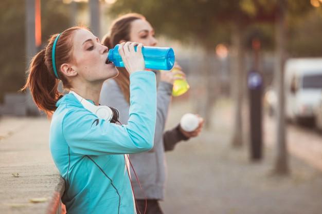 9 alimentos que dan energía y vitalidad: deportistas cansadas bebiendo agua heelespana - HeelEspaña