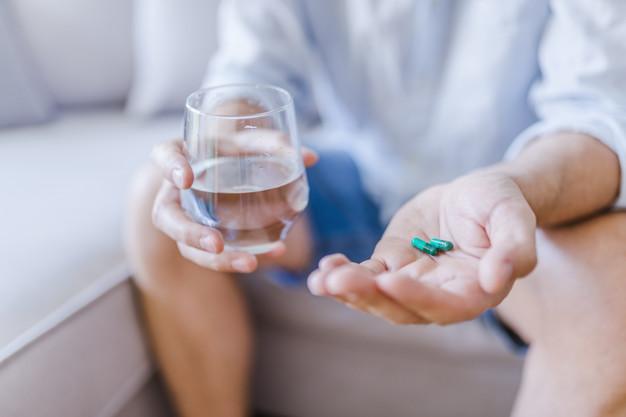 Cuidado con mezclar alcohol y medicamentos: hombre joven pildora vaso agua heelespana - HeelEspaña