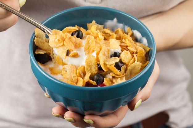 9 alimentos que dan energía y vitalidad: mujer come cereales heelespana - HeelEspaña
