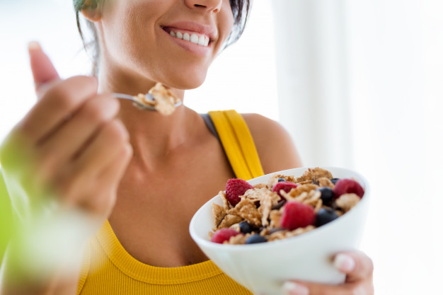 9 alimentos que dan energía y vitalidad: mujer comiendo cereales frutas heelespana - HeelEspaña