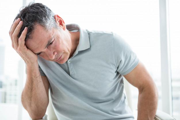 Cuidado con mezclar alcohol y medicamentos: tensado hombre sentado contra ventana heelespana - HeelEspaña