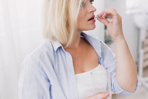 Alimentos que contienen probióticos: mujer toma complemento alimenticio heelespana - HeelEspaña