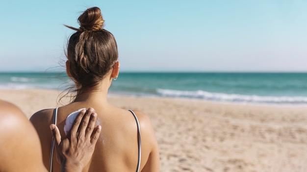 ¿Cómo afecta el calor y la humedad a la piel en verano?: hombre poniendo crema sol espalda - HeelEspaña